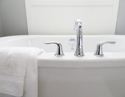 Een mooi zojuist schoongemaakt wit bad met een witte handoek erover geslagen