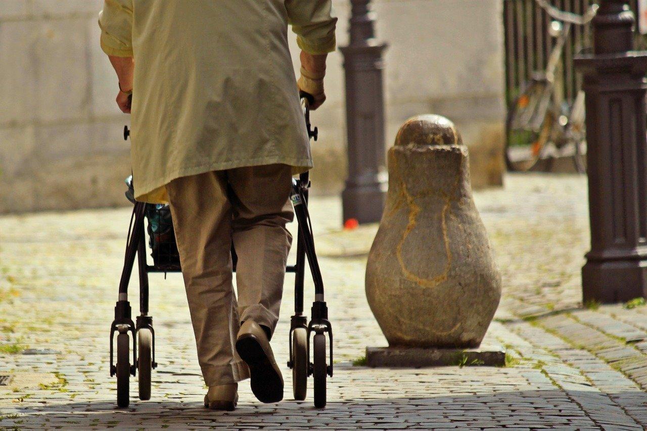 Oude man met beige lange jas die met een rollator loopt over de klinkers
