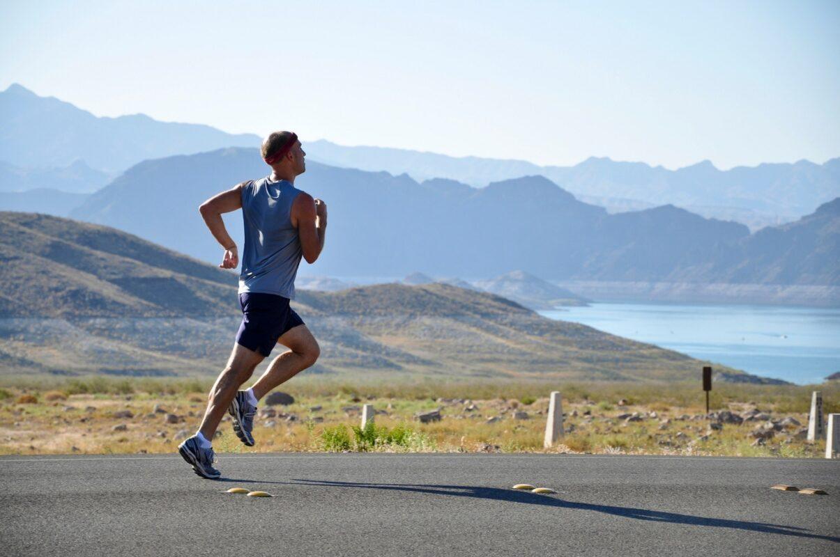 Een man die aan het hardlopen is op de weg langs de zee