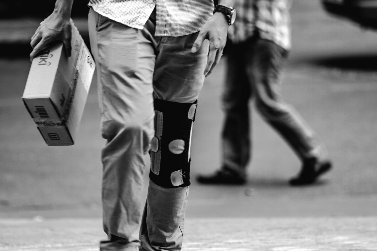 Een man die op straat loopt met een kniebrace