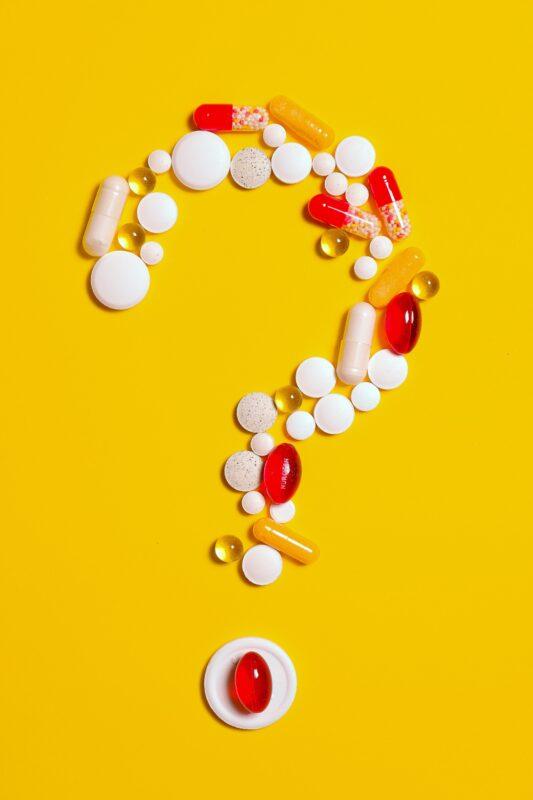 Medicatie in de vorm van een vraagtegen op een gele achtergrond